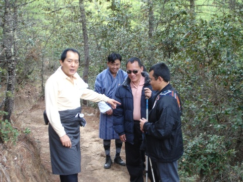 [Photo: The old king chats to Pema and Sanga during a walk in the woods]